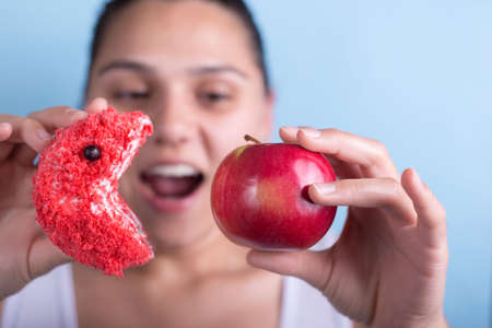 A young girl holds a cake and an apple in her hand, plays with them, the cake tries to eat an apple. Concept of junk food vs healthy Foto de archivo