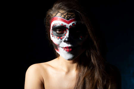 portrait of a Mexican girl in Halloween makeup. On a dark background. Sugar skull girl in hat, studio shot