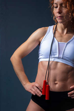 athlete girl with flawless muscles and athletic body, holding a skipping rope, posing against a textured blue wall background Foto de archivo