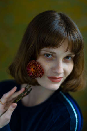 beauty portrait of a young pretty girl holding a wilted red flower near her face, posing at studio over dark background