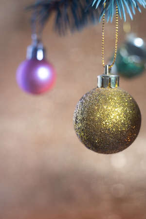 close-up of multi-colored Christmas toys on the fir, on a golden Christmas background Gold tree ornament