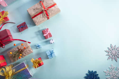 top view, lots of Christmas gifts on a blue background. New year flatlay Beautiful gifts in gold packaging and Christmas balls on blue background Foto de archivo