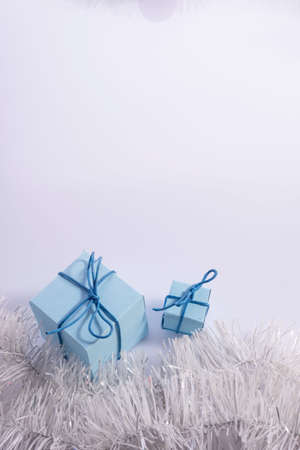 blue Christmas gifts with fir-tree cones, on a white background. vertical shot gift box with white ribbon isolated on white background. Clipping path included. Foto de archivo