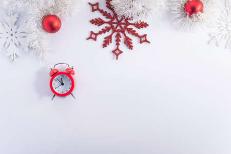 red clock alarm clock on christmas white background, with new year decorations Christmas clock and fir branches covered with snow