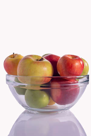 yellow and red green apples in a glass plate. isolate on white background.