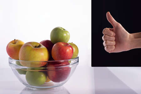 thumb up, on the background of a fruit combination in a plate. On a black and white background confident young sporty hispanic woman holds a fresh apple after a gym session promoting healthy eating and healthy lifestyle