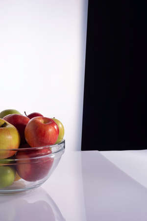 set of different varieties of apples in a transparent glass container. On a black and white background Red apples in a plate on white Foto de archivo
