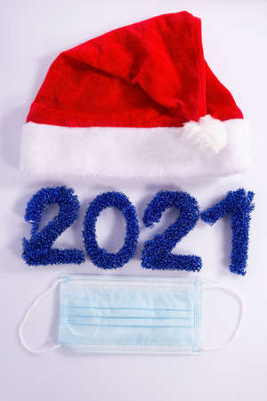 numbers laid out 2021, coronavirus christmas concept. Santa coronavirus Santa Claus hat and beard with face mask on a blue background, creative minimal concept of Christmas and New Year Foto de archivo