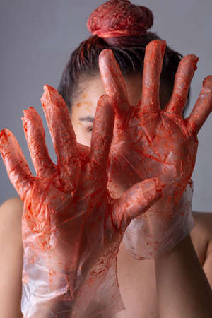 portrait of a girl in gloves soiled in cool paint. Hair dyeing. Beauty hair. On a gray background. Foto de archivo