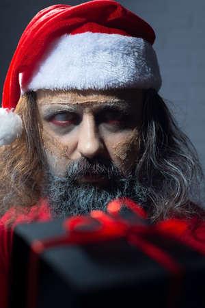 christmas portrait of scary zombie santa dead man. New year horror concept. Halloween zombie santa