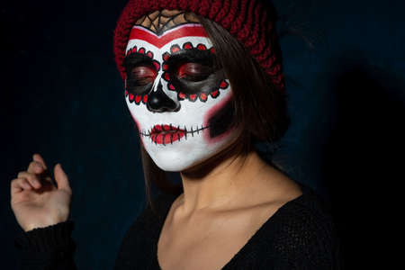 portrait of a Mexican girl in Halloween makeup. On a dark background. Sugar skull girl in hat, studio shot Zdjęcie Seryjne