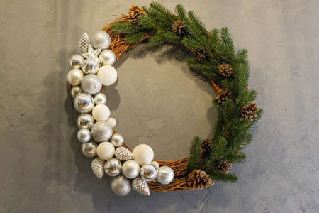 christmas wreath of fir trees with new year toys, on gray concrete background Green christmas wreath decorated with gold balls, lights and pinecones on an old vintage planked wood background - rustic style Zdjęcie Seryjne