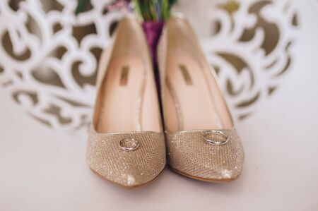 Elegant golden wedding shoes with golden wedding rings on a white chair Standard-Bild