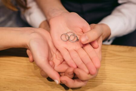 Young couple holds in hands golden wedding rings