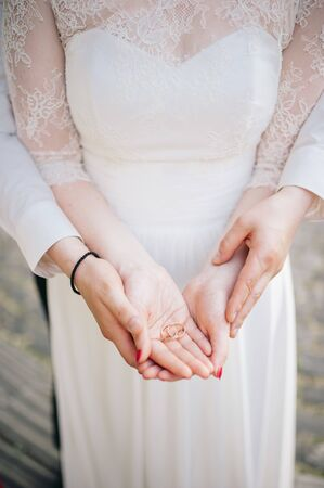 Couple on a wedding day holds wedding rings in hands
