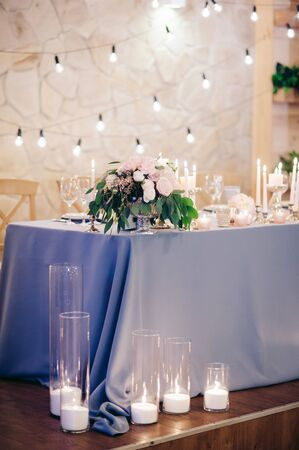 Wedding table beautifully decorated with blue tablecloth, flowers, greenery, candles Standard-Bild