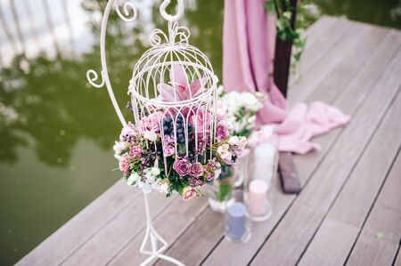 Wedding ceremony area on the river decorated with floral arrangements of greenery and flowers and candles