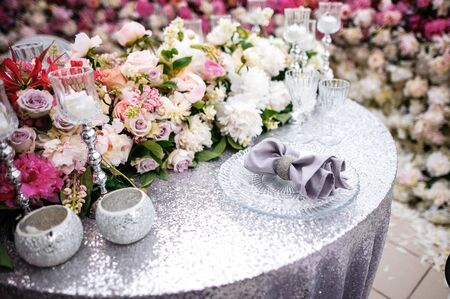 banquet table is decorated with compositions of flowers and greenery, candles, silver tablecloth, plates and napkins