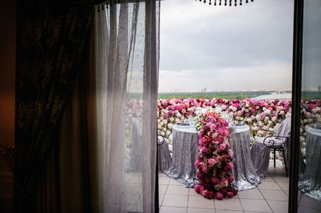 Beautifully decorated table for two stands on a balcony, covered with flowers and silver fabrics