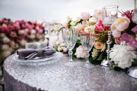 Beautifully decorated table with silver table cloth, plates, napkins, glasses, candles and lot of  pink and whiite flowers