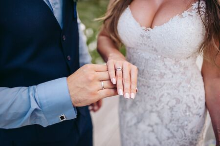 The groom in a suit and the bride in a white dress stand on the background of a green park and hold their hands together, there are wedding rings on their fingers