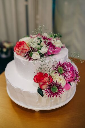 White wedding cake decorated with red and pink flowers and greenery standing on a wooden table Standard-Bild - 140554079