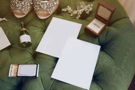 empty sheets of paper lie on a green pouf; next to the bride's shoes; engagement ring; hair jewelry