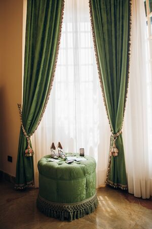 a room in a hotel decorated in green and yellow shades, on a soft puff under the window there are the bride's accessories