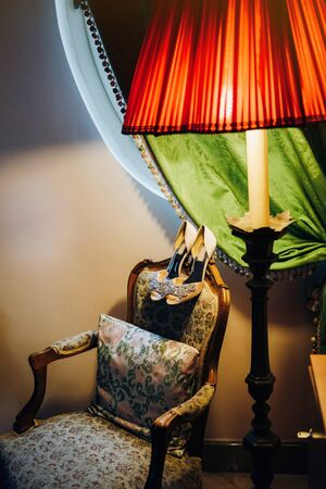 Wedding high-heeled shoes lie on the back of a beautiful chair, the chair stands under a window with a green curtain, next to it is a red lamp Standard-Bild