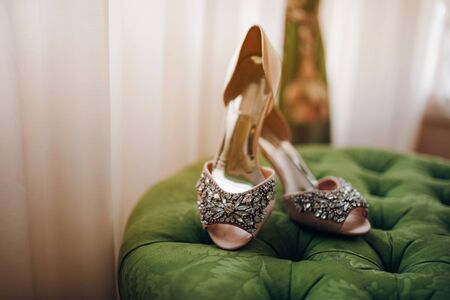 stylish bridal high-heeled shoes decorated with stones stand on a green soft padded stool Standard-Bild
