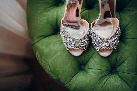 designer wedding shoes decorated with stones stand on a green soft sofa