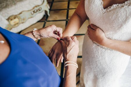 mom helps the bride to fasten jewelry on her hand, close up