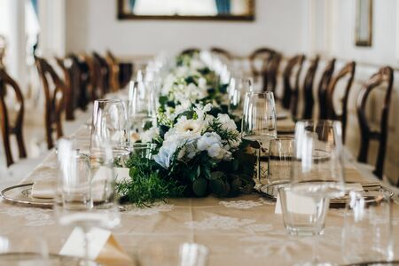 The wedding festive table is decorated with floral arrangements, glasses, plates and cutlery, the table is covered with a beautiful tablecloth Standard-Bild