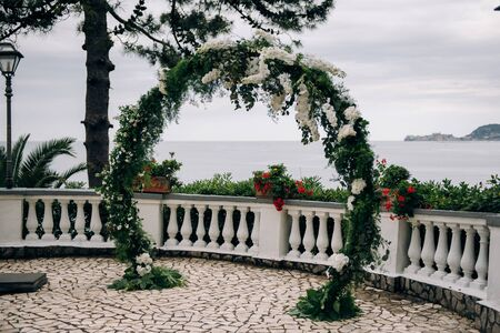 a round wedding arch of greenery and white flowers stands on the balcony overlooking the sea