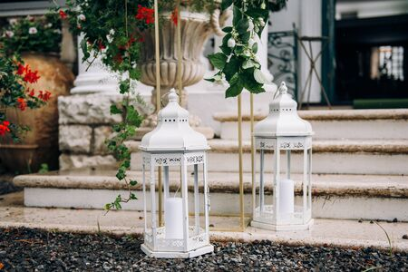 White candle lanterns are standing on the stairs of the house
