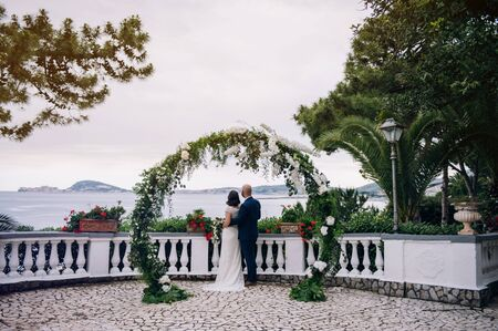 Bride and groom standing on a balcony under round wedding arch made of fresh flowers and greenery overlooking sea Standard-Bild