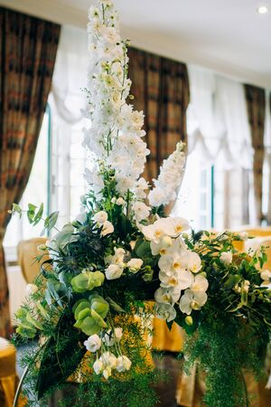 the arrangement of flowers at the wedding stands on a metal stand, consists of many greens and white flowers and orchids Standard-Bild