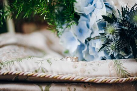 Two wedding rings lie on a pillow, there are fresh blue flowers and greenery