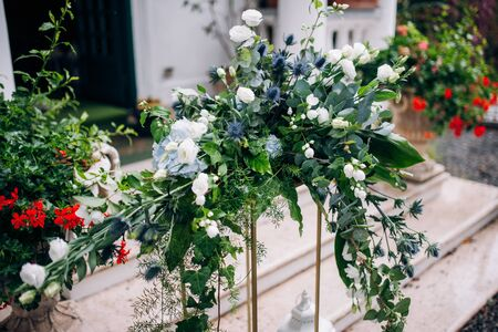 the arrangement of flowers at the wedding stands on a metal high stand, consists of many greens and white flowers