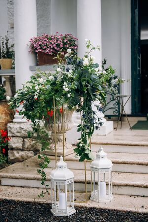 the arrangement of flowers at the wedding stands on a metal high stand, consists of many greens and white flowers stands on the steps of the stairs, next to it there are lanterns with candles Standard-Bild