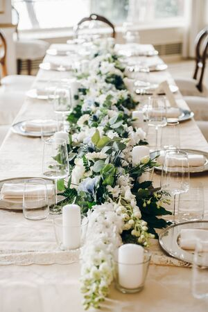 White and green flower composition, candles, plates with napkins, there are on a wedding table covered with tablecloth Standard-Bild