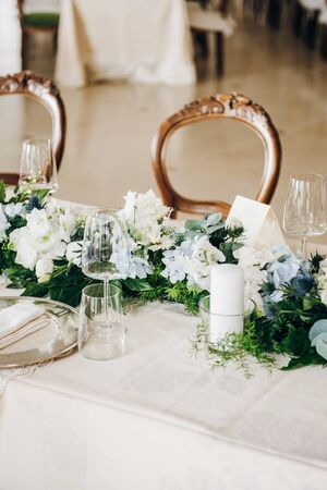 Wedding table decorated with tablecloth, fresh flowers composition, candles, plates and glasses