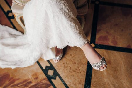 the bride sits on a chair, at the bride's feet there are designer high-heeled shoes decorated with stones Standard-Bild