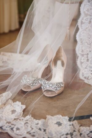 stylish bride's high-heeled shoes, decorated with stones, stand on the floor, next to a white lace veil