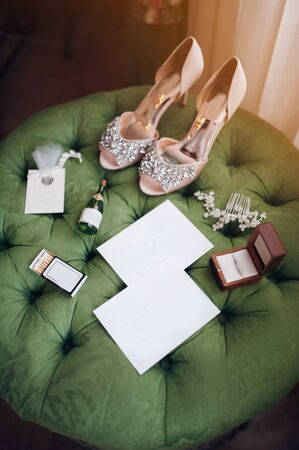 on the green pouffe there are the brides wedding accessories - fashion high-heeled shoes, jewelry, empty invitations, engagement ring
