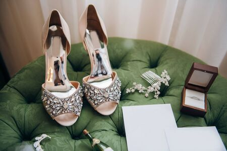 on the green pouffe there are the bride's wedding accessories - fashionable high-heeled shoes, jewelry, empty invitations