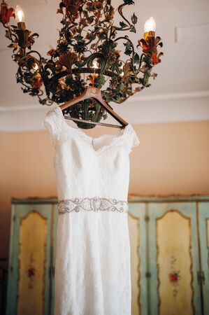 White lace wedding dress with a belt embroidered with stones hanging on a designer chandelier