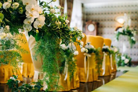 Yellow chairs in the wedding ceremony area are decorated with white orchids and greenery