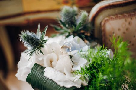 Two golden wedding rings lie on a wedding flowers, the flowers are white and blue with greenery