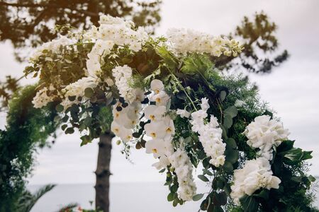 Round wedding arch made of greenery and fresh white flowers standing outside